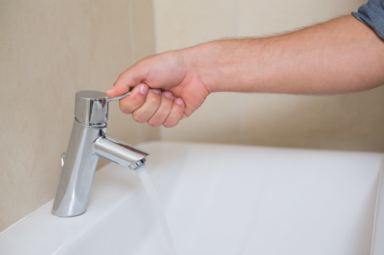 hand turning on faucet