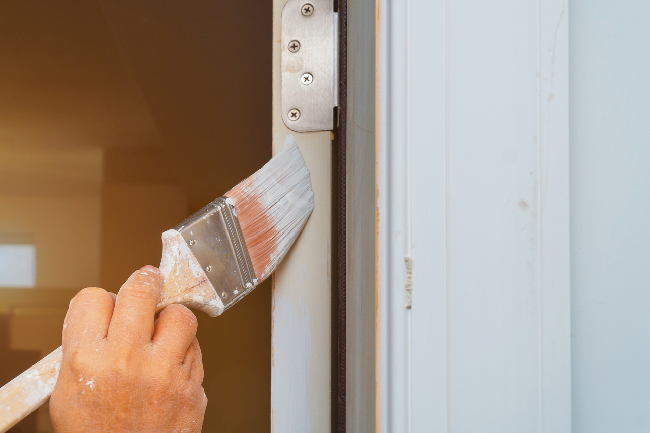 Professional painter cutting in with brush man is painting door with brush
