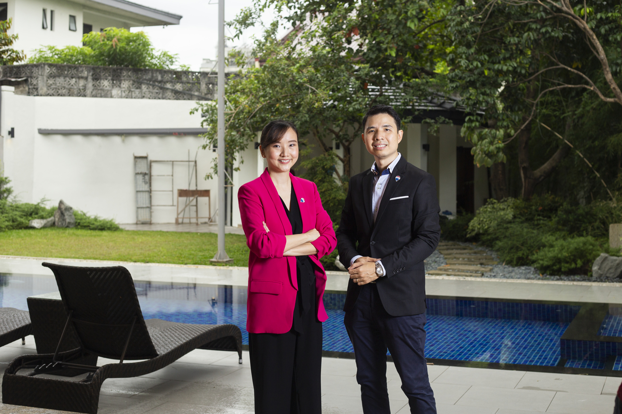 man and woman real estate brokers in front of swimming pool