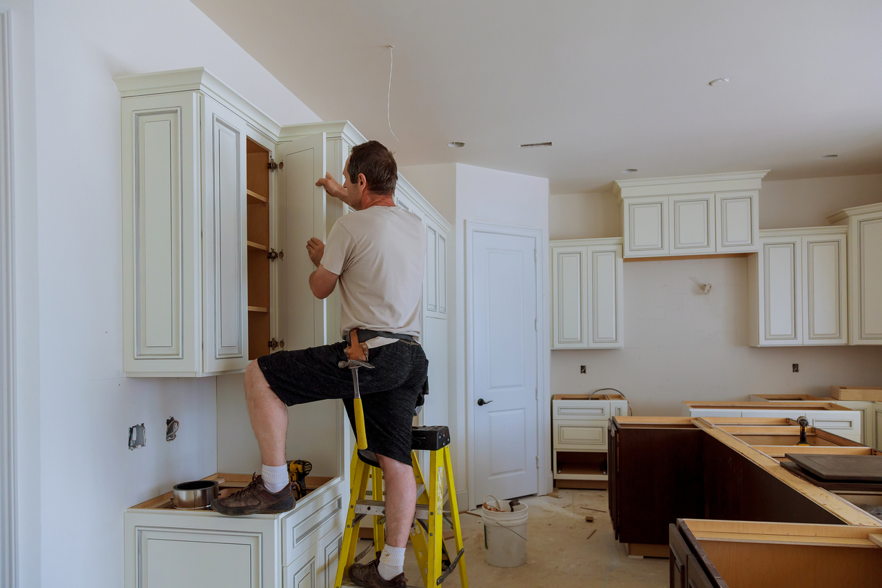 man replacing kitchen cabinets
