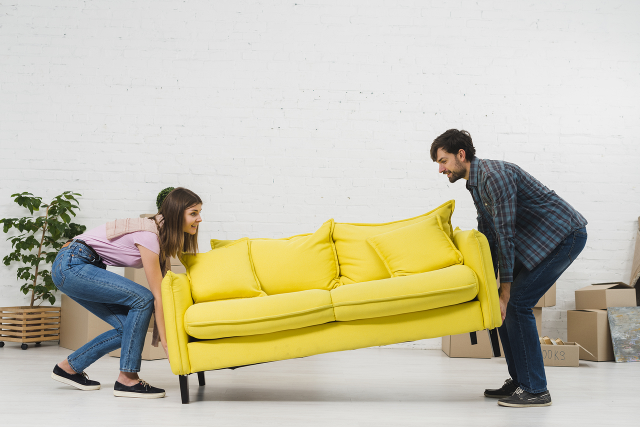 man and woman moving yellow couch