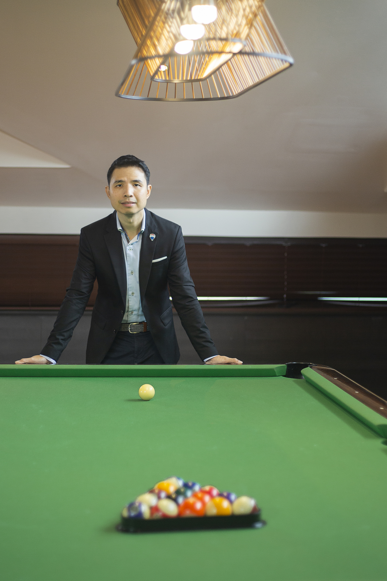 John Yu leaning over a billiards table