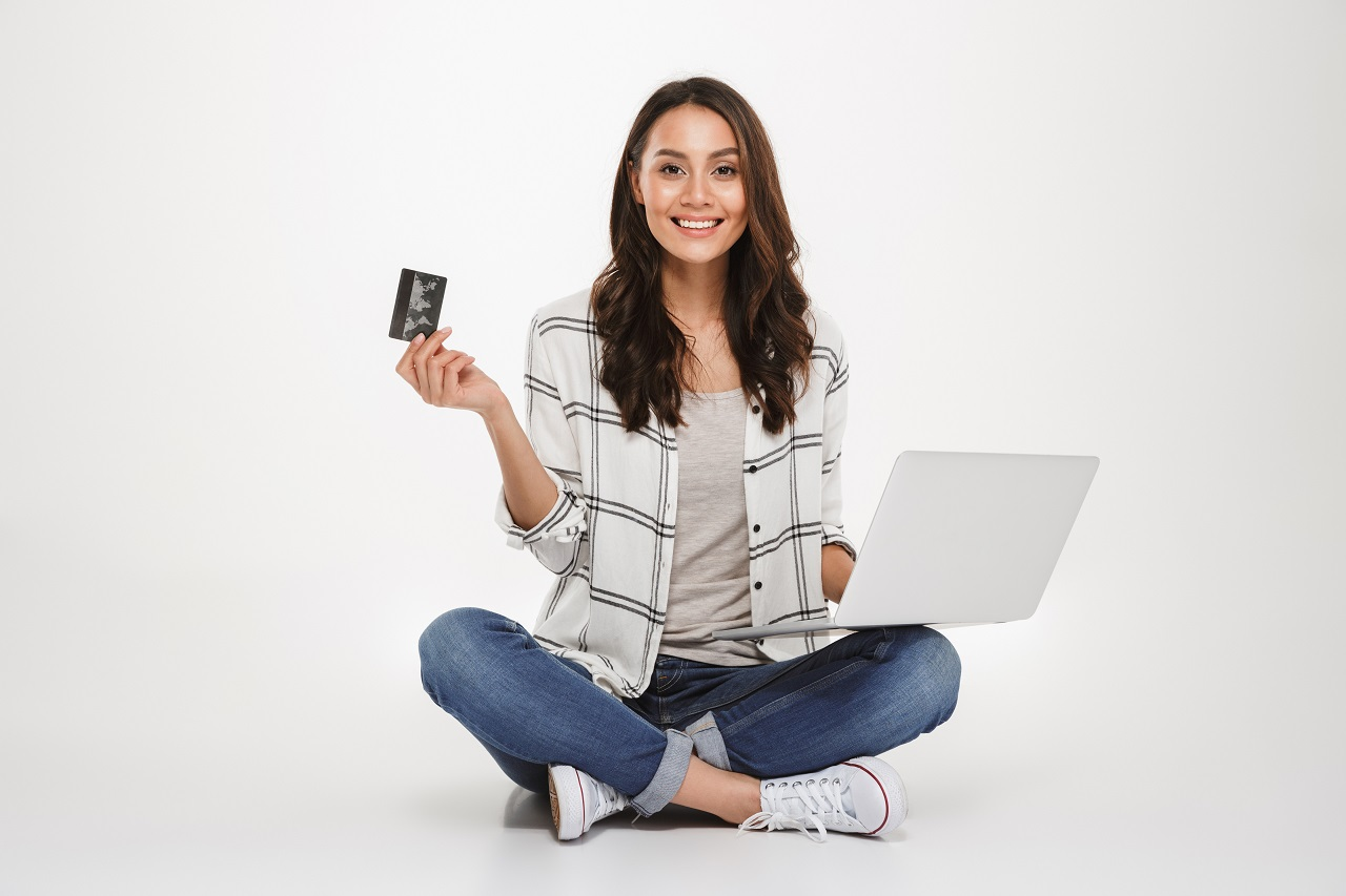 Smiling brunette woman in shirt sitting on the floor with laptop computer and credit card