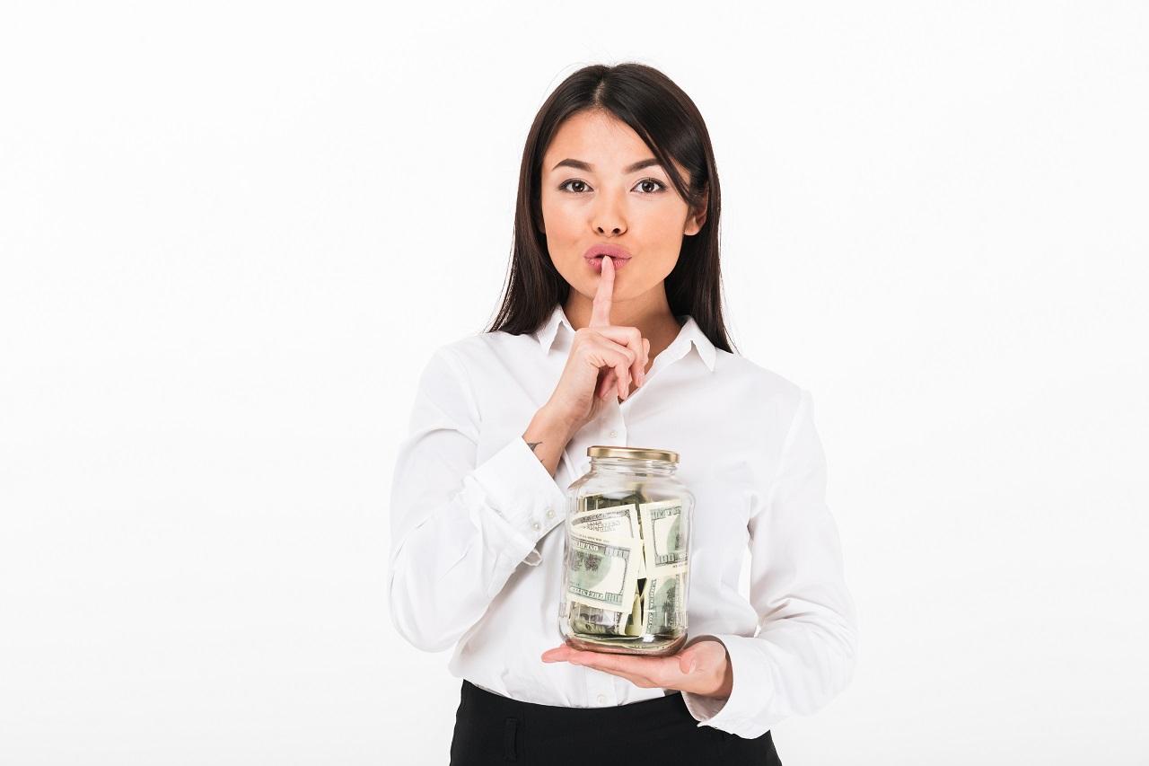 businesswoman holding jar full of money