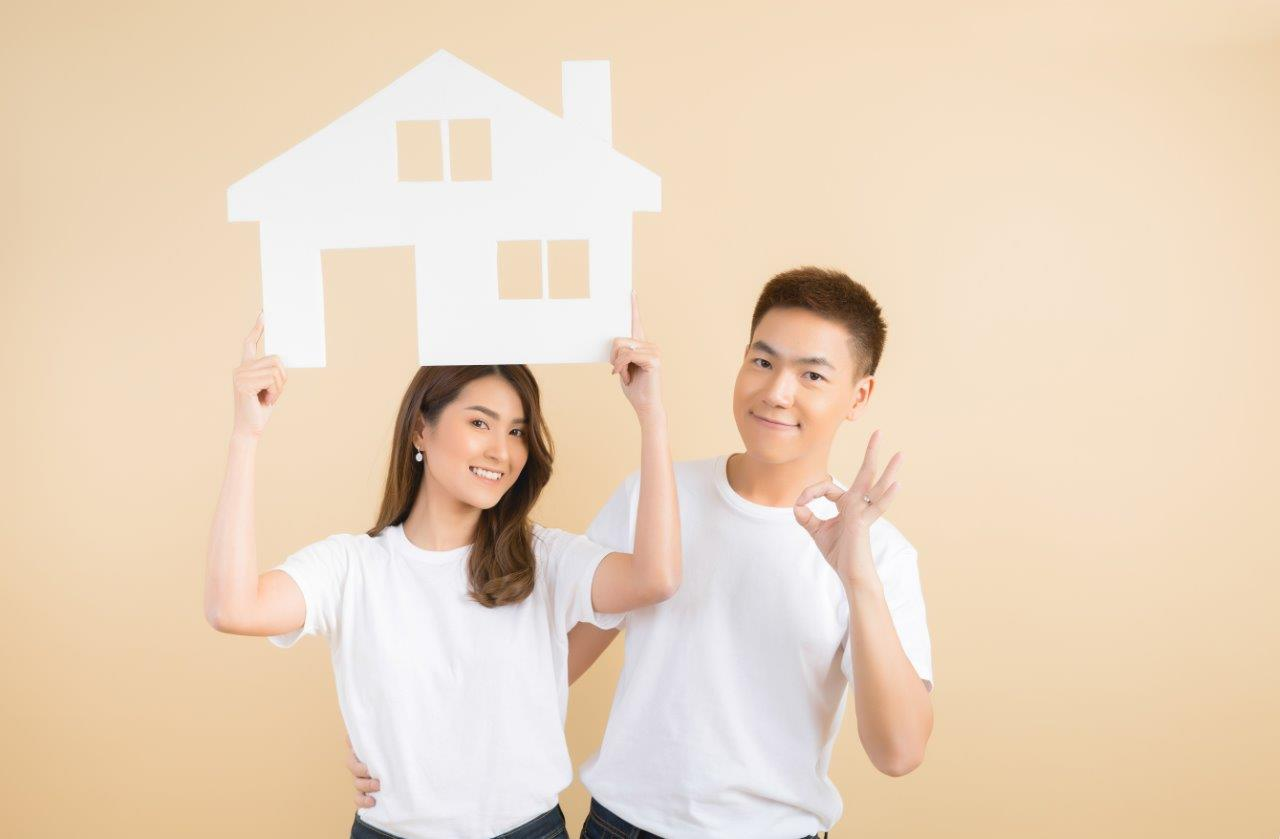 man and woman holding house cutout