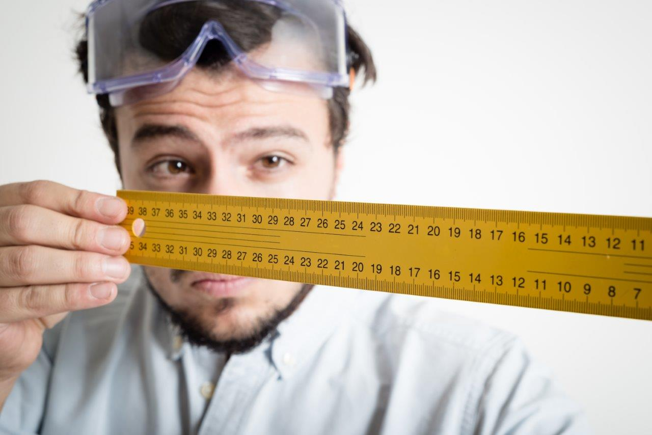 man looking down a ruler