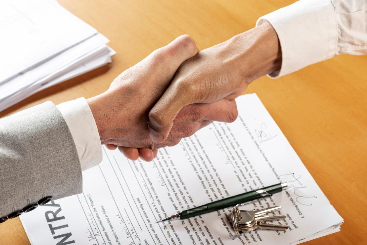 two hands shaking over contract