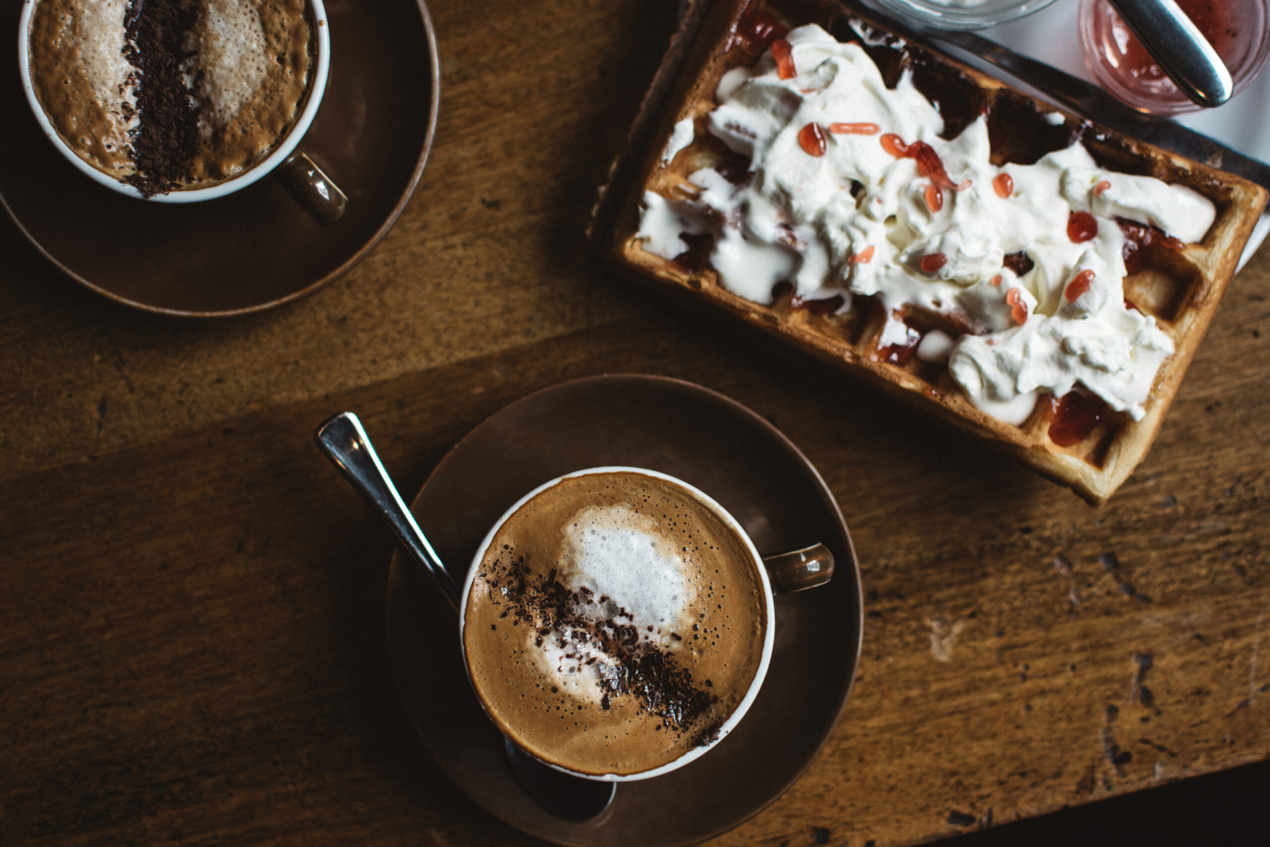 Wooden desk with two cappuccinos and waffle